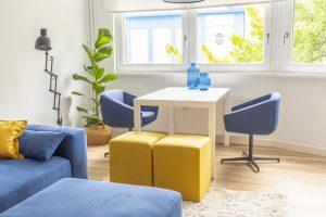 Essecke mit weißem Tisch und blauen Drehsesseln